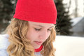 Teenage girl with red winter cap young caucasian curly blond hair and knit outdoors in Stock Images