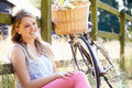 Teenage girl relaxing on cycle ride in countryside sitting by fence smiling Royalty Free Stock Photos