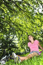 Teenage girl relaxing in a park with her bicycle Royalty Free Stock Images