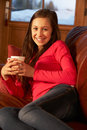 Teenage Girl Relaxing On Sofa With Hot Drink Stock Images