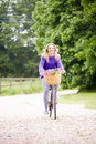 Teenage girl riding bike along country lane with colorful flowers in basket smiling Stock Images