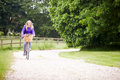 Teenage girl riding bike along country lane by herself smiling to camera Stock Images