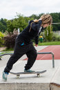 Teenage girl riding her skateboard with dreadlocks at skatepark Stock Photography