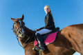 Teenage girl riding a horse on background of blue sky Stock Photo