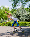 Teenage girl roller blading in a skate park passing the camera at speed with her hands raised the air Royalty Free Stock Images