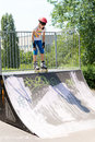 Teenage girl on a roller skating ramp poised at the top as she prepares to launch herself downwards to perform aerobatics Royalty Free Stock Photos