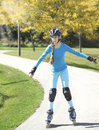 Teenage girl rollerskating in park autumn Royalty Free Stock Photo