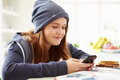Teenage girl sending text message whilst studying at home Stock Image