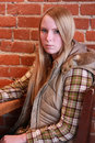 Teenage girl with serious look seventeen year old sitting at a table in a restaurant wearing plaid shirt and parka vest Stock Photo