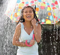 Teenage girl sheltering from rain beneath umbrella smiling Stock Photos