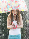Teenage girl sheltering from rain beneath umbrella smiling Royalty Free Stock Photos
