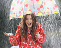 Teenage girl sheltering from rain beneath umbrella smiling Stock Images