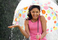 Teenage girl sheltering from rain beneath umbrella smiling Royalty Free Stock Images