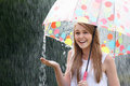 Teenage girl sheltering from rain beneath umbrella smiling Stock Photo