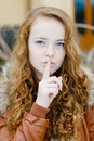 Teenage girl showing silence sign on autumn day Royalty Free Stock Photo