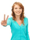Teenage girl showing victory sign bright picture of Royalty Free Stock Photo