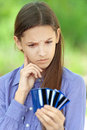 Teenage girl shows credit card sad against green of summer park Stock Image
