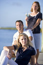 Teenage girl sitting on dock by water with parents Royalty Free Stock Images