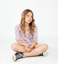 Teenage girl sitting on the floor with sad face smiling Stock Photo