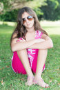 Teenage girl sitting in the grass wearing sunglassses Royalty Free Stock Photo