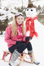 Teenage Girl With Sledge Next To Snowman Stock Images