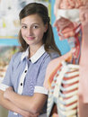 Teenage girl standing by anatomical model portrait of high school student Stock Images