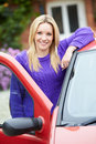 Teenage girl standing next to car holding key looking at camera smiling Royalty Free Stock Photography