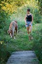 Teenage girl stands with a little horse near a narrow country wooden footbridge Royalty Free Stock Photo