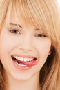 Teenage girl sticking out her tongue health and beauty concept or licking lips Stock Image