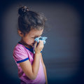 Teenage girl suffers runny nose sneezing handkerchief on a gray background cross process Royalty Free Stock Photos