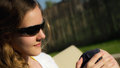 Teenage girl in sunglasses portrait of a positive cheerful sitting outdoors wearing staring at the sun thinking positively Royalty Free Stock Photo