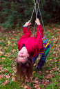 Teenage girl swinging down head in autumn Stock Photography