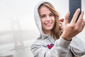 Teenage girl taking selfie portrait of blonde smiling in gray jacket with hood holding mobile phone or ipad to take a white Stock Photos