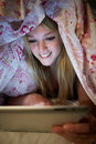 Teenage girl using digital tablet in bed at night under duvet Royalty Free Stock Images