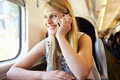 Teenage girl using mobile phone on train journey smiling Royalty Free Stock Photos