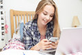 Teenage Girl Using Mobile Phone Whilst Doing Homework Royalty Free Stock Photo