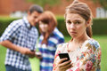 Teenage girl victim of bullying by text messaging unhappy message Stock Photo