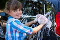Teenage girl washing a car on a sunny day Royalty Free Stock Photo