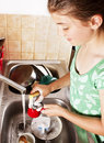 Teenage girl washing dishes in her kitchen Royalty Free Stock Photo