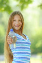 Teenage girl with water bottle beautiful in blue blouse against green of summer park Stock Image