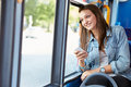 Teenage girl wearing earphones listening to music on bus looking out of window smiling Stock Images