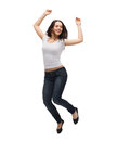 Teenage girl in white blank t shirt jumping activity and happiness concept smiling Royalty Free Stock Image