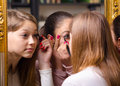 Teenage girlfriends having fun while putting make up beautiful in front of the old mirror Stock Photography