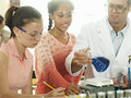 Teenage girls doing science experiment at desk in classroom teacher assisting smiling Royalty Free Stock Photos