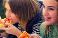 Teenage girls eating pizza in fast food restaurant Royalty Free Stock Photo