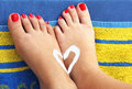 Teenage girls feet on an beach towel with sunlotion heart summer holidays Stock Images