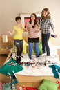 Teenage Girls Hanging Out In Untidy Bedroom Stock Image