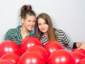 Teenage girls with many red balloons Royalty Free Stock Image