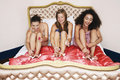Teenage girls painting toenails on bed three in pajamas funky at slumber party Royalty Free Stock Photos