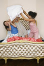 Teenage girls pillow fighting on bed view of three funky Royalty Free Stock Images